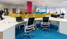 Modern, bright, open plan offices. Blue, yellow & bright pink colours. Office design by Interaction.