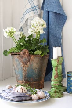 I love these green candlesticks and white geranium in a rusty bucket.