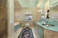 Bathroom featuring aquamarine countertops and glass paneling, matched with beige wood and tile flooring.