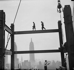 IronWorkers traversing an i-beam spanner.