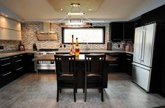 awesome double wide- kitchen with dark lower cabinets, glass tile backsplash & stainless appliances