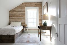 Here's another example of a sash, cottage pane window framed with reclaimed timber planks. The reclaimed wooden bed mirrors the rustic theme of the room, while the fresh white walls and trim bring together light and warm elements for a room that is modern and fresh.