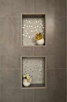 Up close view of shower cutouts with glistening tile and light trim to hold…