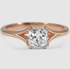 At once feminine and contemporary, this ring divides into graceful ribbons of rose gold that intertwine and embrace the center diamond.