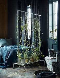 Create a lush room divider! Use a clothing rack such as IKEA RIGGA. Place pots on the rack at the bottom or use string to attach the pot to the frame. Fasten a few branches to the top bar with thread.