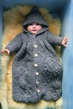 Dual cardigan sleep bag  A knitted sleep bag in smooth, compact yarn is easily unbuttoned to create a separate cardigan. A pointed hood with decorative tassel completes the look. Realise in a chunky cable knit for a home-spun appearance.
