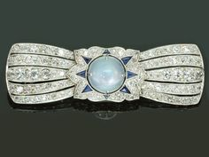 Belle Epoque Art Deco diamond sapphire moonstone platinum brooch. Something between Art Deco and Belle Époque - Art Deco is an eclectic artistic and design style which had its origins in Paris in the first decades of the 20th century. The style originated in the 1920s and continued to be employed until after World War II. c 1920