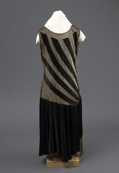 Evening dress, ca 1924, Black satin crepe and gold lamé dress with a drop waistline, gold beads, shift dress, sleeveless, scoop neckline, belt scarf from the waist with tassle beads.