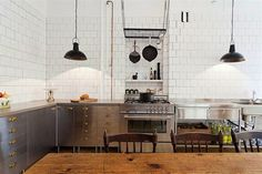 An industrial kitchen in Stockholm featuring stainless steel drawers and sink. The kitchen has unconventional storage in the form of a hanging pot rack and vintage wooden crates.