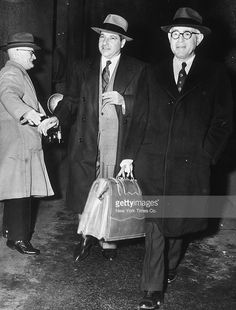 Feb. 13, 1951: Full-length image of Italian-born gangster Frank Costello (Francesco Castiglia, 1891-1973) entering the Federal Building with his attorney, George Wolf (R), to participate in the Senate Crime Committee hearing, Washington, DC. At left is a photographer.