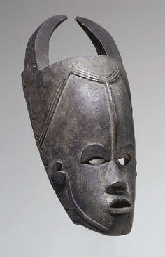 A BETE OR GURO MASK  By the Masters of Gonate  With pierced eyes below arched brows in relief, pierced open mouth, median ridge to the center of the tall forehead, triple groove to the angled hairline, small ears in shallow relief, two horns above of rectangular section curving inwards to almost joined at the tips, encrusted dark patina, old labels 17¾in. (45cm.) high