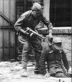 A Russian soldier pulls a German from a manhole April 1945. Reminiscent of the capture of Saddam Hussein in Iraq December 2003.