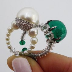 Superb pair of rings by Bombay contemporary jeweller Viren Bhagat. Natural 15mm diameter pearl ring, with pearl hoop and briolette-cut diamond terminals and a 15 carat cabochon emerald ring with diamond rondelle hoop and emerald bead terminals. To be sold in Geneva 18 May.