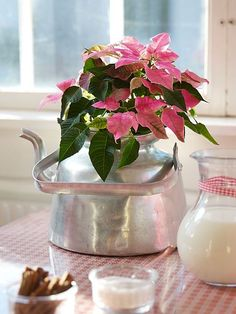 Metallic finishes --- such as this silver teakettle --- are brilliant holiday accents, especially for non-traditional poinsettia colors.