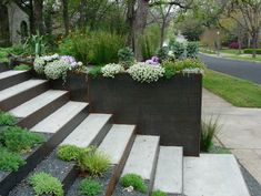 Corten steel, concrete and gravel steps create sculptural beauty and anchor tiered landscaping.