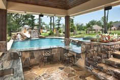 Bossier City Pool Design, Shreveport Pool Construction - natural-grotto-dolphin-slide-outdoor-kitchen-granite-bar-tanning-ledge-perimeter-spa