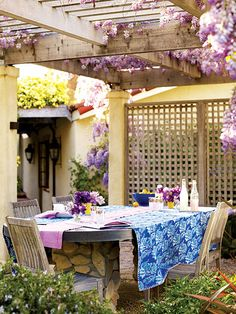 This spacious patio in Saratoga, California is a great spot for intimate suppers with its ceiling of wisteria and lattice walls. The table was custom built with a copper top and a base of twin stone pillars.