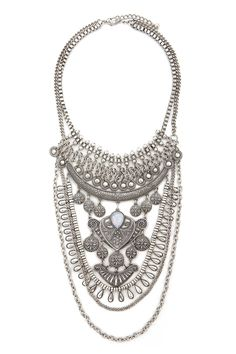 A burnished statement necklace featuring etched, faux gem, medallions, and ornate designs on curb and box chains, and a lobster clasp closure.