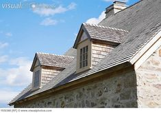 View Of The Cedar Shingles Roof And Dormer Windows On An Old Canadiana Cottage Style Fieldstone Residential Home Quebec Canada