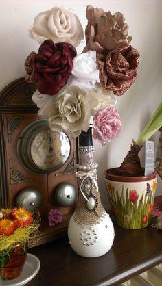 Bottiglia decorata e fiori di stoffa.