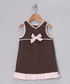 Traces of pink and a bow offset the classic woolen texture of this dress for a look that is simply darling.