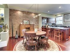 Exposed brick detail and a bar that opens to the kitchen makes this a true gathering space