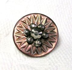A Victorian era iridescent Mother-Of-Pearl shell button with a carved, radiating pattern. One large cut steel in the center surrounded by six smaller cut steels.