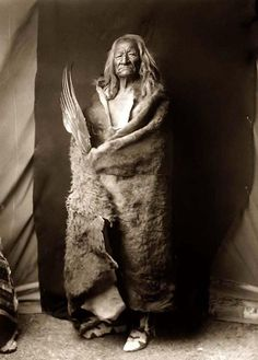 Black Eagle in a full-length portrait, standing, facing front, and wearing buffalo hide and holding the wing of bird