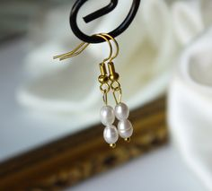 delicate ivory white freshwater rice pearl gold fish hook dangle earrings. $4.99, via Etsy.