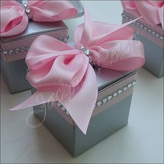 Our silver wedding favor boxes feature a pink satin bow and rhinestones to fill with candy or treats with a touch of bling. Bridal shower or 25th Anniversary party guests will love the decorative touch to your tables.  Featured here in a one piece silver box accented with pink satin ribbon, a large hand made satin four loop bow and real silver rhinestone accents.  Try filling with Godiva Gem truffles (each box holds up to 4), one gourmet truffle, classic jordan almonds, 90 jelly beans, 70…