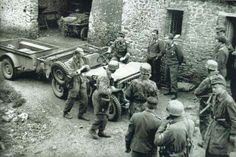 A handful of Fallschirmjager from 14th Kompanie-1st Fallschirm. Regt  , a JEEP with its trailor, a windfall for the Fallschirmjager who had no transportation vehicle,Saint-Lô, France 1944.