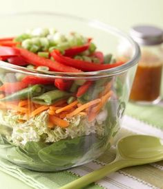 Layered Asian Salad: Sweet, citrusy homemade dressing adds amazing flavor to a veggie layer salad. More potluck salads: http://www.midwestliving.com/food/salads/20-delicious-potluck-salad-recipes/