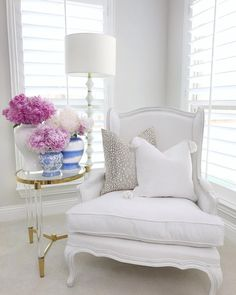 Bedroom inspiration, sitting area, white french wingback chair, white restoration hardware chair , lucite gold round accent table, round side table, gold floor lamp, white furniture, peonies in ginger jar, watercolor ginger jar, antelope pillow, tassel pillow, neutral bedroom