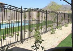 faux wrought iron fence Here's a decorative wrought iron pool fence with arched tops.
