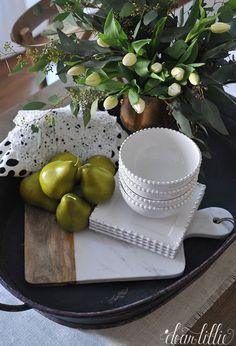 Fresh flowers mixed with some fresh or faux fruit like these pears from HomeGoods help add bright and cheery touch to a kitchen or dining room. Grouping items all together like on this large tray help make for a great and easy little vignette. (sponsored pin)