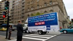 A rolling billboard sponsored by Citizens for Tax Justice (CTJ), reading: 'Do you pay more Federal Income Taxes than Facebook, Southwest Airlines, GE, Pepco and other Giant Corporations? Yes You Do!' A CTJ report, 'Ten Reasons We Need Corporate Tax Reform,' crosses an intersection April 15, 2013 in Washington, DC.