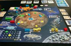 """""""Alien Frontiers"""" is a game of resource management and planetary development for two to four players. During the game you will utilize orbital facilities and alien technology to build colony domes in strategic locations to control the newly discovered world. The game board shows the planet, its moon, the stations in orbit around the planet, and the solar system's star. The dice you are given at the start of the game represent the space ships in your fleet. You will assign these ships to the…"""