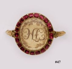 Garnet, silver, and gold memorial ring. Early 19th century red garnets set in yellow gold with a center of braided hair in the form of an initial.  This would normally commemorate the birth or the passing of a child.