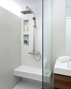 """petite salle de bains claire avec un carrelage mural en gris clair et blanc, pomme de douche """"pluie"""" et paroi de douche en verre"""