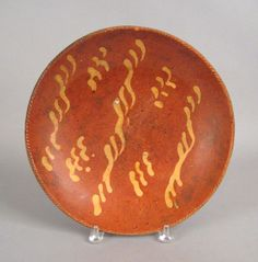 """Pook & Pook. October 24th & 25th 2008. Lot 171.  Estimated: $400 - $800. Realized Price: $644. Redware charger, 19th c., with yellow slip decoration, 12 1/2"""" dia."""