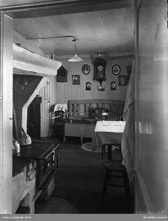 Interiör från Södertälje vid Nygatan 31, Turingegatan 19-21 och Kaplansgatan 14-16 i kvarteret Flugan 2 och 3. Östra byggnaden utmed Turingegatan. Köket i bottenvåningen med vedspis, kökssoffa och matbord. På väggen porträtt och väggur.