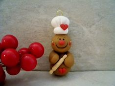 A little gingerbread man is holding a tiny rolling pin!    This is an original design that has been handcrafted from polymer clay. The