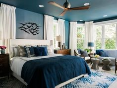 Rich navy blue walls with crisp white accents and a global influence creates a captivating master bedroom with beautiful views and designated spaces for rest and relaxation. >> http://www.hgtv.com/design/hgtv-dream-home/2017/master-bedroom-pictures-from-hgtv-dream-home-2017-pictures?soc=pinterest