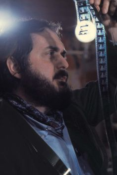 Stanley Kubrick analysing a 35mm strip of film from A Clockwork Orange, 1971. Photographer, Dmitri Kasterine.