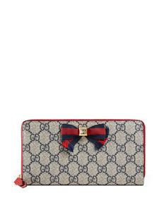 Gucci GG supreme canvas wallet with leather trim. Striped grosgrain bow with a golden-framed black Swarovski crystal center. Zip-around top closure. Center zip compartment. Interior, three bill and 12