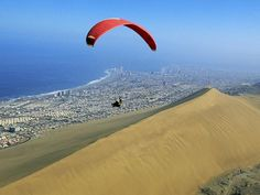 Paraglider Above Atacama Desert  Photograph by Joel Sartore    A paraglider rides the winds above the Cerro Dragon sand dune in Chile's Atacama Desert. The coastal desert occupies a long strip between the Pacific Ocean and the Andes Mountains. Parts of it have never had a recorded rainfall.