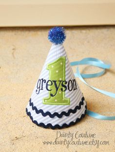 Boys First Birthday Party Hat - Dapper blue and white stripes with green and navy blue accents - Free personalization. $25.00, via Etsy.    Love this idea, but without the age so that he can use it year after year.