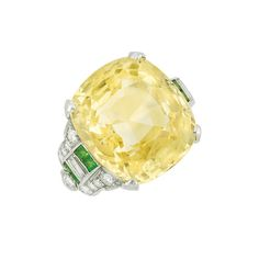 Art Deco Platinum, Yellow Sapphire, Diamond and Demantoid Garnet Ring Centering one cushion-shaped yellow sapphire approximately 20.25 cts., flanked by 2 baguette diamonds and 8 square-cut demantoid garnets, edged by 18 old European and single-cut diamonds, circa 1925