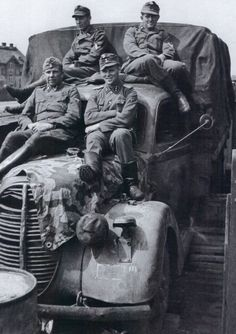 """Loading men and vehicles at the Tschudowo station. This Ford G917T has suffered as a result of being stationed at the front. The SS Obersturmführer must be the commander of 13. Kompanie/SS-Infanterie-Regiment 9 """"Thule"""". Of note is the use of a Wehrmacht Splinter A Zeltbahn covering the engine bonnet."""