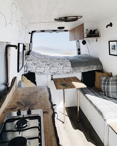 camper van with live-edge counters, upholstered banquette in gray, white, and wood